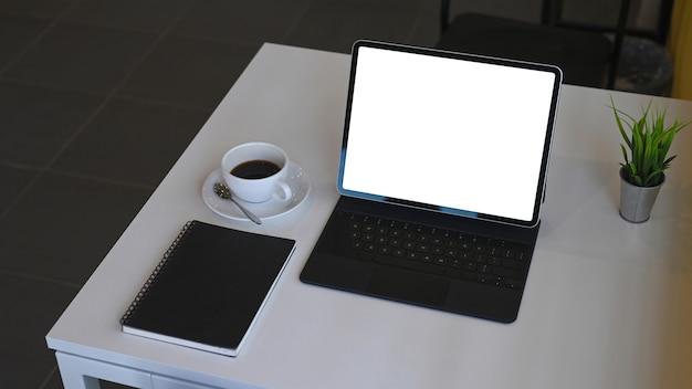 Mock up tablet digitale con tastiera wireless, tazza di caffè, taccuino e pianta della casa sul tavolo bianco.
