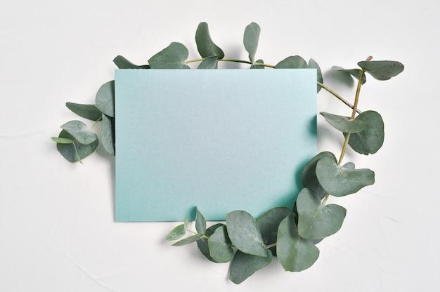 Manichino di foglie di eucalipto e foglio di carta turchese con posto per testo su sfondo bianco