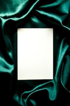 Mock up saluti digitando sfondo panno di seta di colore verde, carta bianca composizione piatta per biglietti di auguri immagine della stagione copia spazio