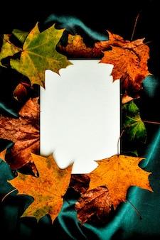 Mock up saluti digitando sfondo panno di seta di colore verde con foglie autunnali, carta bianca e foglie autunnali composizione piatta per biglietti di auguri immagine della stagione copia spazio