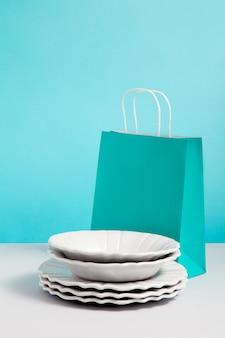 Derida sull'immagine con stoviglie ceramiche vicino al supporto del sacco di carta su fondo blu. immagine di concetto del regalo con spazio per il disegno. negozio di regali. branding mock up. concetto per vendite o sconti, promozione