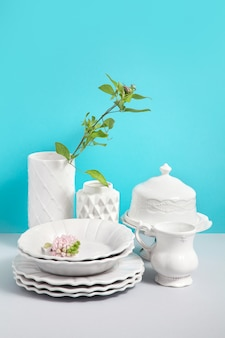 Derida sull'immagine con stoviglie bianche per servire e vasi di fiori sulla tavola grigia su sfondo blu con spazio per il design. immagine per negozi di stoviglie in ceramica. concetto di natura morta.