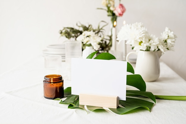 Mock up label the blank menu frame in bar restaurant, stand for booklets with white paper, wooden tent card on monstera leaf on restaurant table