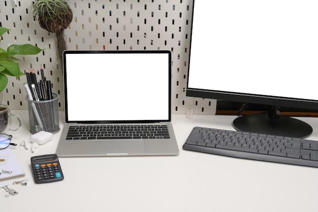 Mock up laptop, calcolatrice, pianta d'appartamento e portamatite sulla scrivania bianca.