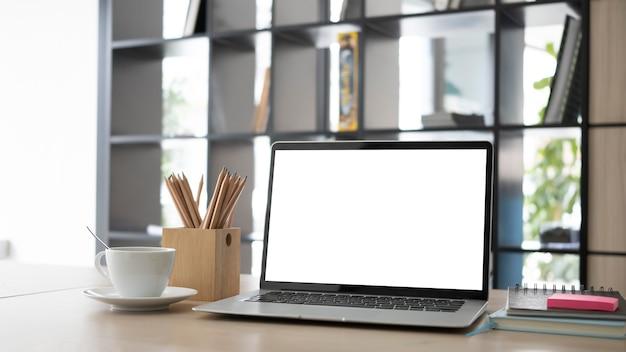 Mock up computer portatile, portamatite e tazza di caffè sulla scrivania in legno.