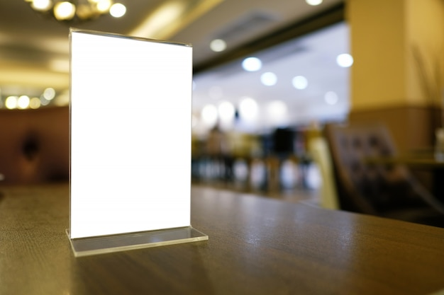 Mock up cornice di menu in piedi sul tavolo di legno nel bar ristorante bar. spazio per il testo.