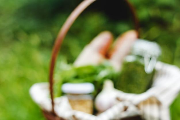 Mock up fuori fuoco del cestino da picnic italiano con cibo baguette pane pesto salsa sfocata estate