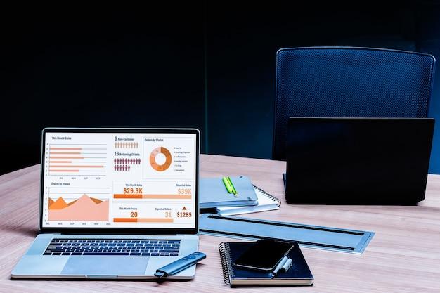 Mock up presentazione presentazione riepilogo vendite su display laptop con notebook sul tavolo nella sala riunioni