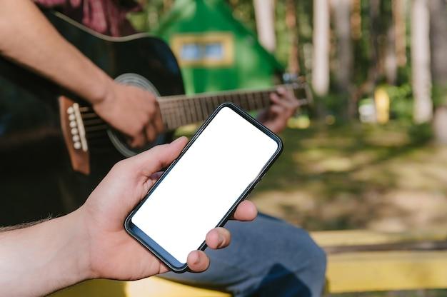 Mock up di uno smartphone davanti a un uomo che suona la chitarra. sullo sfondo della foresta e delle case in natura.