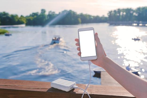 Mock up di uno smartphone nella mano di una ragazza sul molo. ricarica il tuo telefono con power bank. sullo sfondo del fiume, lago con una barca.