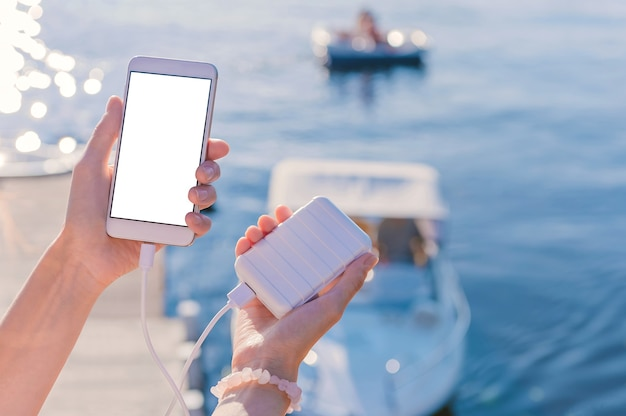 Mock-up di uno smartphone nelle mani di una ragazza sul molo. ricarica il tuo telefono con power bank. sullo sfondo di un fiume, lago, baia, con barche e uno yacht.