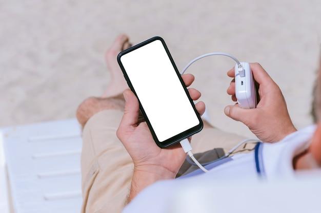 Un mock-up di uno smartphone nelle mani di un ragazzo con un caricabatterie di power bank. sullo sfondo della spiaggia di sabbia.