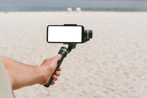 Un mock-up di uno smartphone su una steadicam nella mano di un uomo. sullo sfondo di una spiaggia di sabbia.