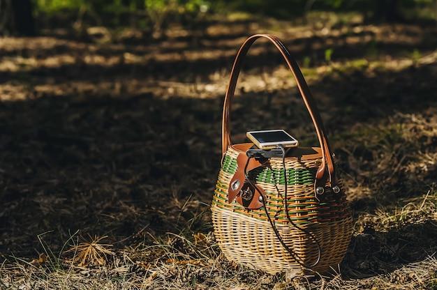 Mock up di uno smartphone con power bank in carica su un cestino nella foresta. concetto sul tema della ricreazione all'aperto.