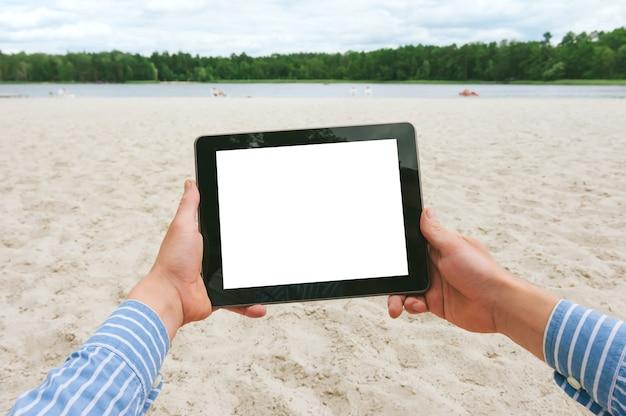 Mock up tablet nelle mani di un uomo. sullo sfondo del fiume spiaggia e foresta.