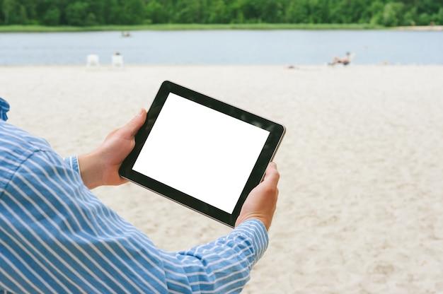 Mock up tablet nelle mani di un uomo. sullo sfondo della spiaggia e del fiume.