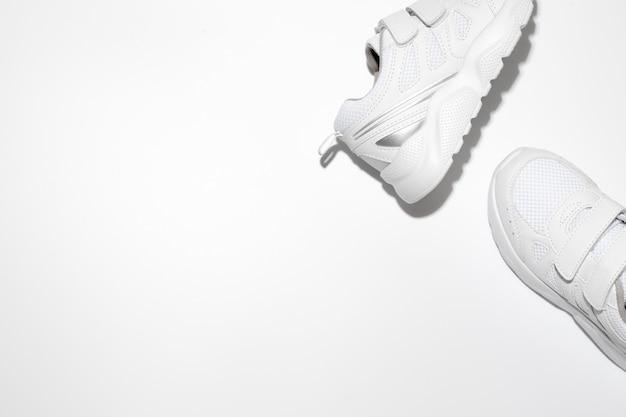 Metti in mostra due scarpe da corsa bianche sul lato con spazio libero per il testo isolato su uno sfondo bianco