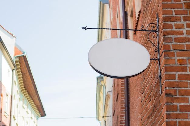 Mock up di un cerchio vintage ovale vuoto vuoto bianco per caffè, nome del ristorante e logo, in una città vecchia