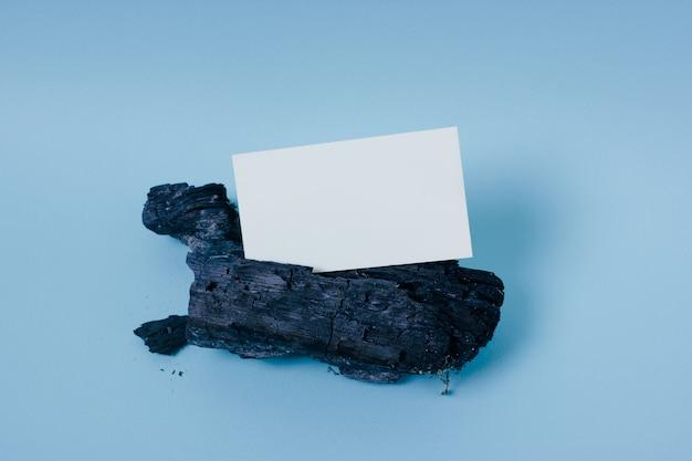 Derida sul biglietto da visita bianco su un pezzo di legno carbonizzato sul blu
