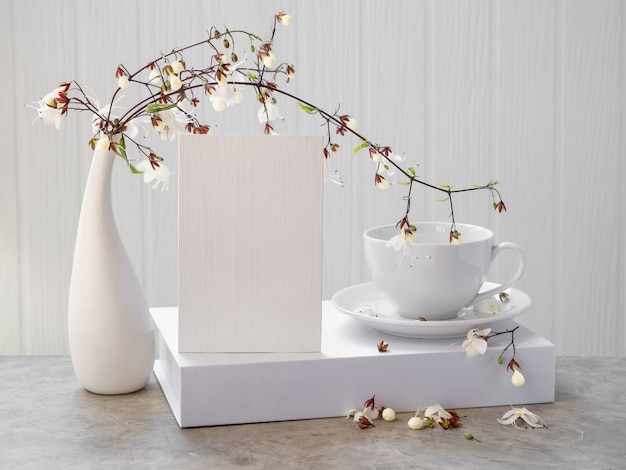Mock up biglietto d'invito bianco, tazza di caffè e bellissimi fiori di clerodendron annuendo in vaso moderno impostato sul tavolo di cemento