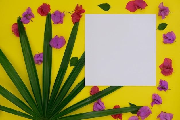 Libro bianco di modello con spazio per testo o immagine su sfondo giallo e foglia di palma e fiore tropicale.