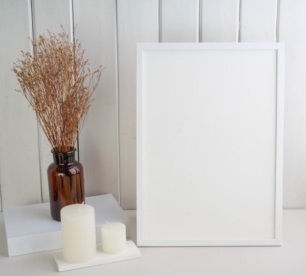 Mock up cornice bianca per poster, candele e bellissimi fiori secchi lagurus ovatus in una moderna composizione di vasi di vetro su tavolo in legno bianco interno