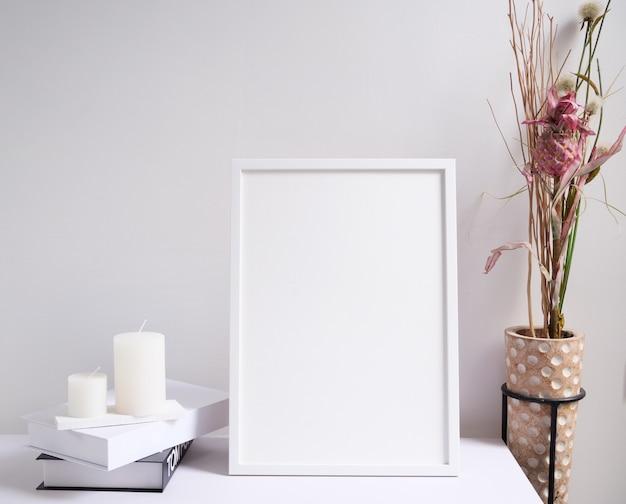 Mock up cornice bianca per poster, candele, libro e bellissimi fiori secchi in una moderna composizione di vasi in legno su un tavolo in legno bianco interno della stanza