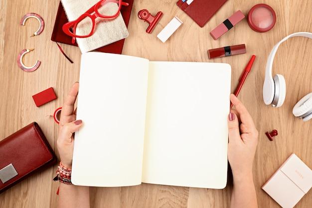 Mock up donna mano che scrive in taccuino vuoto e stazionario ufficio rosso. vista piana laico e dall'alto. giornale di piallatura, disegno. creatività, concetto di home office