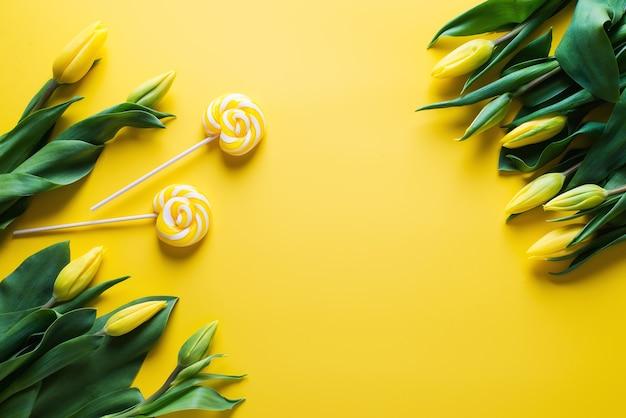 Mock up di tulipani gialli con lecca-lecca su sfondo giallo, copia dello spazio