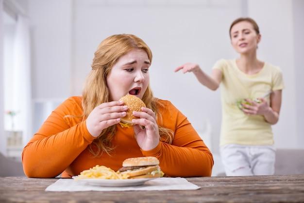 Beffa. donna robusta infelice che mangia un panino e il suo amico sottile che la critica