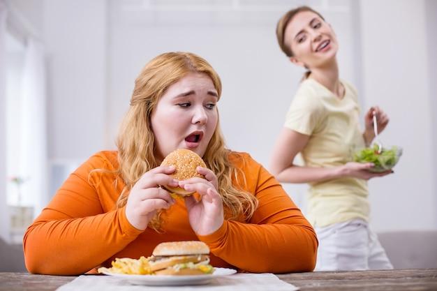 Beffardo. povera donna robusta che mangia un panino e la sua sottile amica sorride