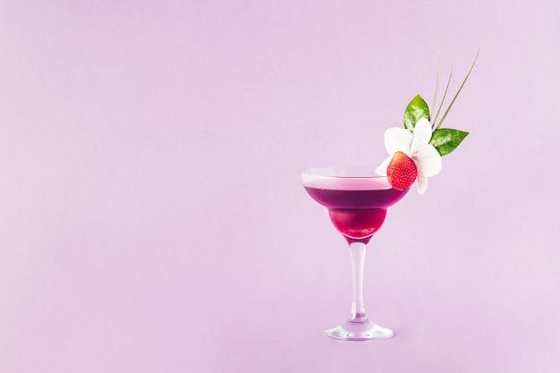 Mocktail decorato con fragole, fiori e foglie tropicali
