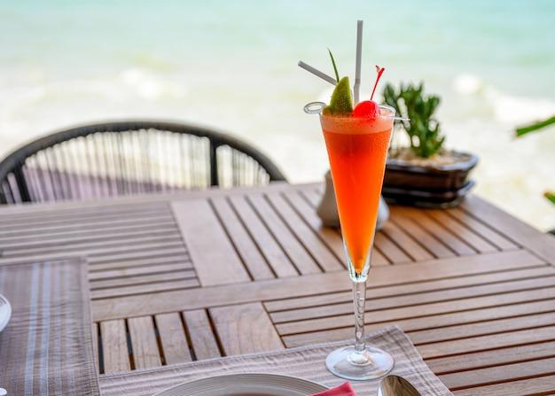 Mocktail frutti misti con lime e ciliegia sul tavolo da pranzo in legno