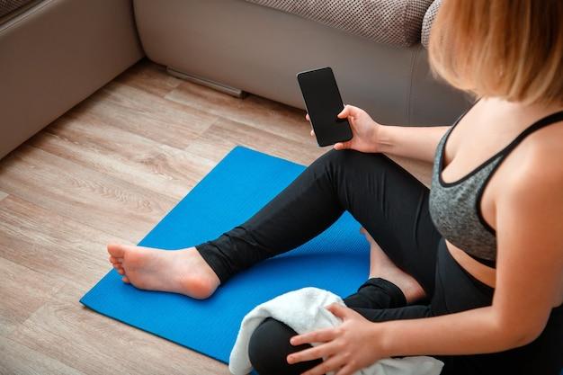 Mockup per programma di fitness online app, lezione di yoga a distanza. donna in abbigliamento sportivo che tiene in mano uno smartphone con schermo vuoto per app per lo sport o la musica durante una pausa di allenamento sul tappetino a casa.