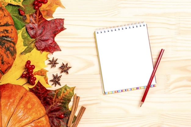 Mockup composizione autunnale. carta in bianco e matita, zucche e foglie su fondo in legno.