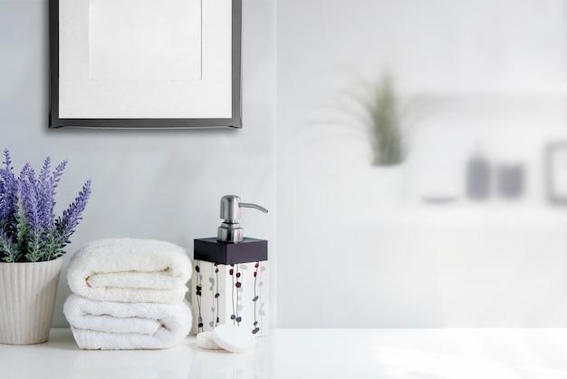 Asciugamano di bagno modello con bottiglia di sapone liquido e houseplant sul tavolo bianco nella stanza bianca.