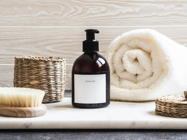 Mockup per prodotti da bagno in bagno, shampoo spa, bagnoschiuma, sapone liquido con un asciugamano accanto e accessori vari