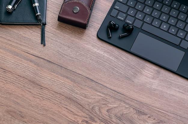 Mockup di tastiera nera, auricolare, borsa in pelle, penna e taccuino sulla tavola di legno, vista dall'alto.