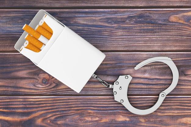 Pacchetto di sigarette vuoto mockup incatenato alle manette di metallo su uno sfondo di tavolo in legno. rendering 3d