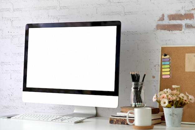 Computer desktop dello schermo in bianco del modello sul tavolo. area di lavoro a casa studio