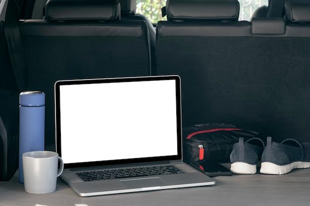 Computer portatile con schermo vuoto mockup sul retro dell'auto, concetto di lavoro all'aperto.