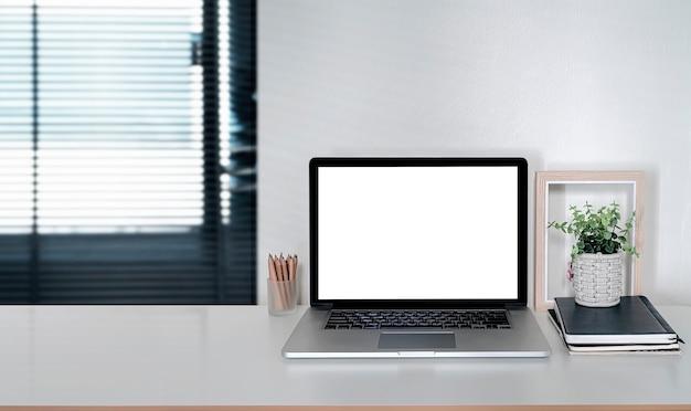 Computer portatile dello schermo in bianco del mockup sul tavolo bianco nella stanza dell'ufficio moderno, spazio della copia.