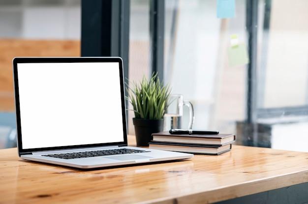 Computer portatile dello schermo in bianco del modello sulla tavola di legno nell'area di lavoro congiunta.
