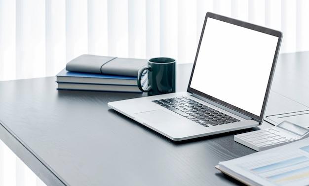 Computer portatile dello schermo in bianco del modello sulla tavola di legno nella stanza moderna dell'ufficio.