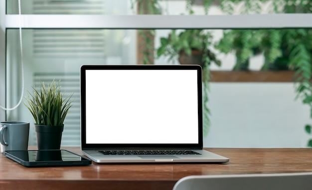 Computer portatile dello schermo in bianco del modello sulla tavola di legno con il fondo della pianta verde.