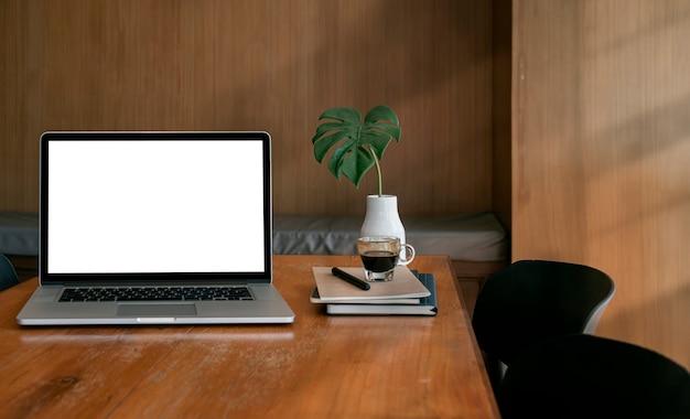 Computer portatile dello schermo in bianco del modello sulla tavola di legno nella stanza di legno dell'ufficio. comodo ufficio a casa.