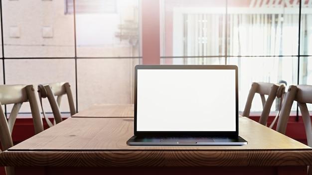 Computer portatile dello schermo in bianco del modello sul tavolo dello scrittorio in caffetteria