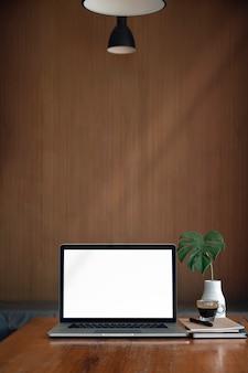 Computer portatile dello schermo in bianco del modello sulla tavola di legno in caffetteria, vista verticale.