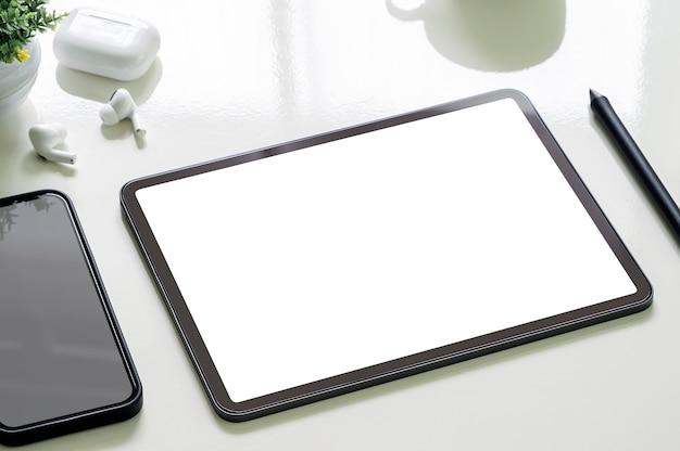 Compressa e smartphone portatili dello schermo in bianco del modello sulla tavola superiore bianca.