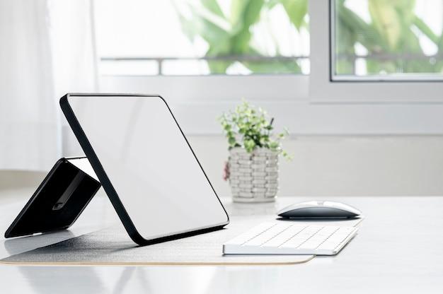 Tablet portatile con schermo vuoto mockup sul tavolo con sfondo chiaro.